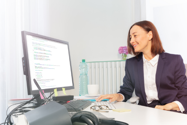 Business woman smiling and looking at code on her monitor