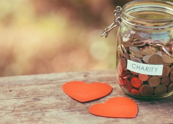 Charity glass jar with coins and two red cardboard hearts on table