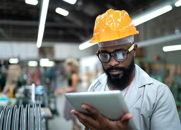 Man with hardhat looking at ipad