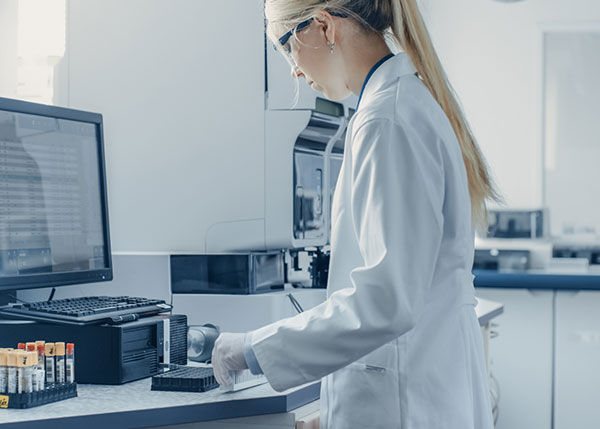Woman in lab coat working on computer